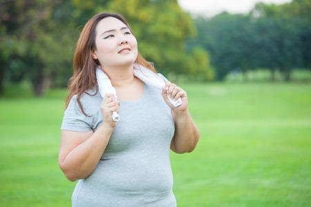 幸せな脂肪アジア フィット女性がポーズ屋外公園内