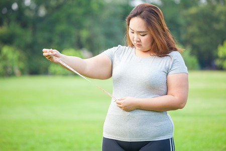 measuring: Happy fat asian woman measuring her stomach in the park Stock Photo
