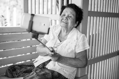senior asian: Black and white image of Happy senior woman posing for a selfie at home
