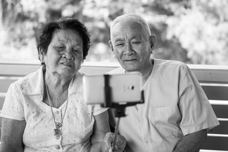 taking a wife: Black and white image of Happy senior couple posing for a selfie at home