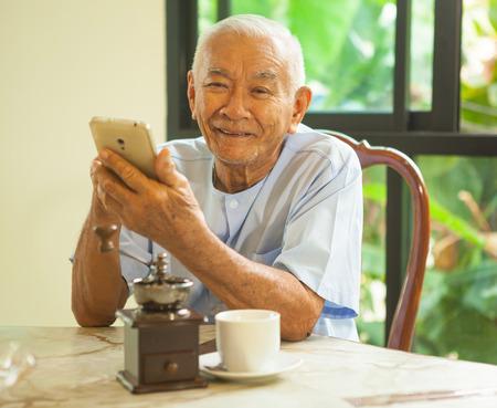 Šťastný asijské starší muž pomocí mobilního telefonu v domácnosti
