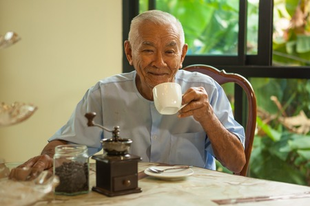 senior asian: Asian senior man with vintage coffee grinder and coffee beans