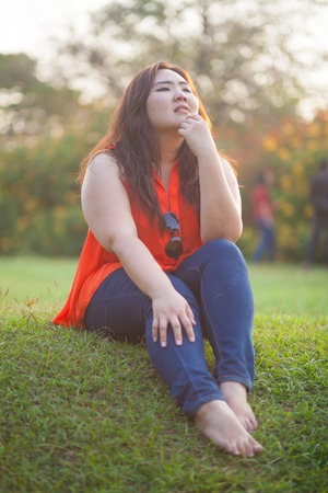 plus size woman: Happy fatty asian woman posing outdoor in a park