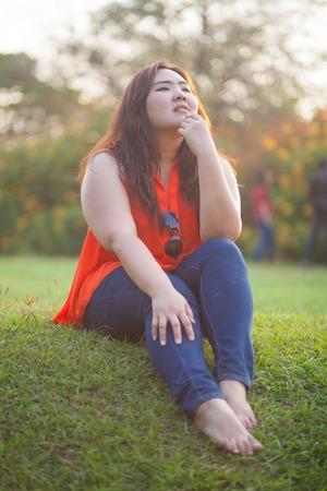 mujer gorda: Mujer asi�tica posando al aire libre graso feliz en un parque Foto de archivo