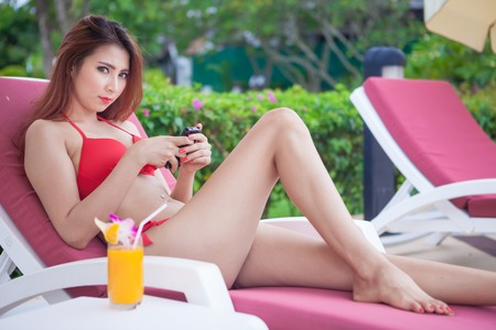 Beautiful young asian woman relaxing on sunbed with smart phone photo