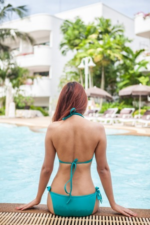 sexy asian girl: Sexy asian girl in blue bikini sitting near swimming pool