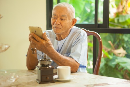 senior adult men: Happy asian senior man using the mobile phone in home Stock Photo