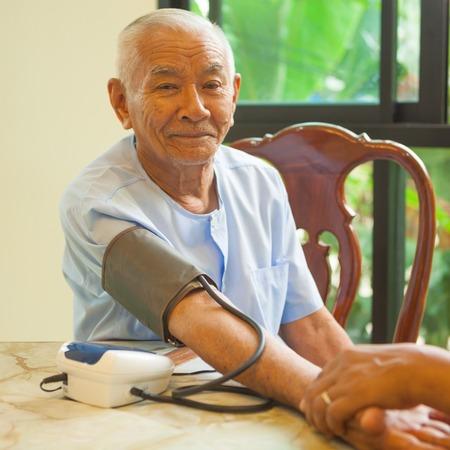 doctor measuring blood pressure of senior asian man patient