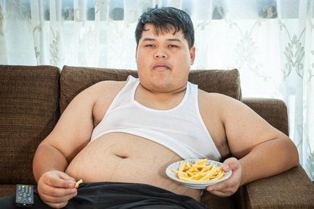man couch: Lazy overweight asian male sitting with fast food on couch and watching television