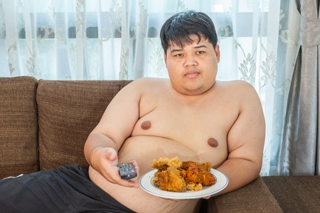 Lazy overweight asian male with fast food and watching television Stock Photo