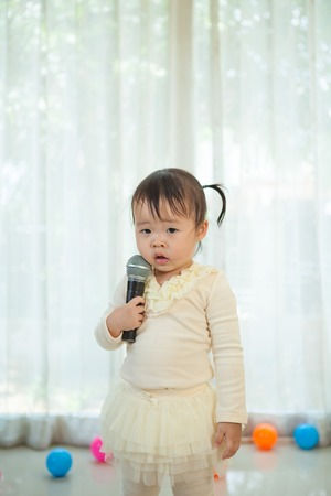 Happy little asian girl with microphone in the home photo