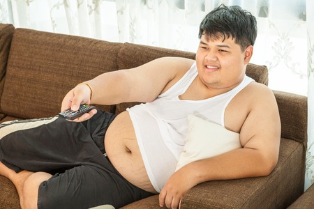 sedentary: Overweight asian guy sitting on the couch with remote in hand trying to watch some TV Stock Photo