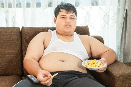 couch potato: Lazy overweight asian male sitting with fast food on couch and watching television