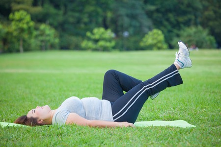 Asian fat woman lying by exercise leg upwards at the park
