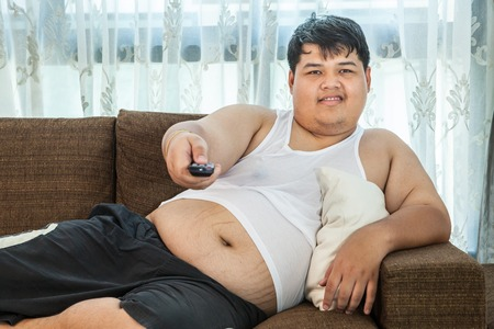 obesity: Overweight asian guy sitting on the couch with remote in hand trying to watch some TV Stock Photo