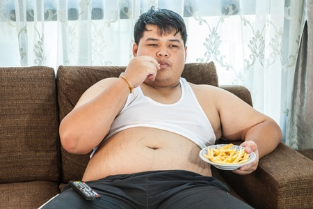 junk: Lazy overweight asian male sitting with fast food on couch and watching television