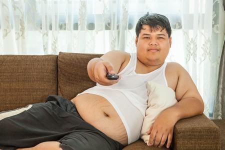sedentario: Chico gordo que se sienta en el sofá para ver la televisión