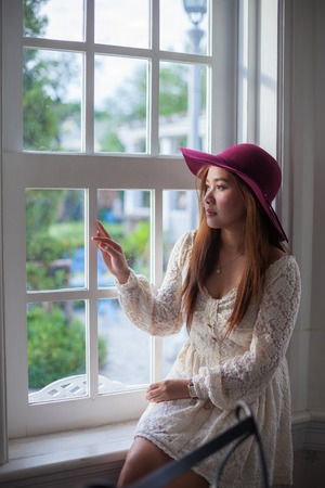 think out: Sad asian vintage woman on the window looking out the window Stock Photo