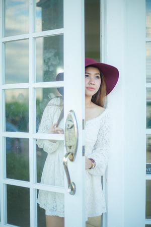 niña pensando: Triste mujer asiática vintage que mira por la puerta