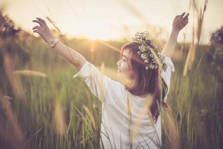 personas de pie: mujer asiática joven que presenta en campo de oro en la puesta del sol Foto de archivo