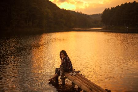 見事な夕日を見て桟橋に座っている女性
