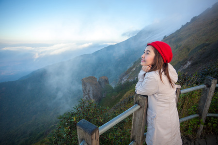mist: Young woman on a cliff overlooking the mountains with fog, Thailand Stock Photo