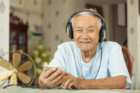 Happy asian senior man Headphones Listening Music at home