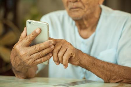 家で携帯電話を使用して幸せなアジア シニア男 写真素材
