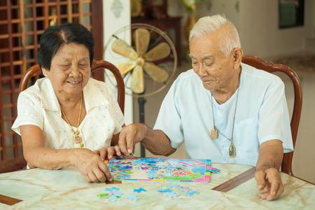 家でジグソー パズルで遊んでアジア カップル シニア 写真素材
