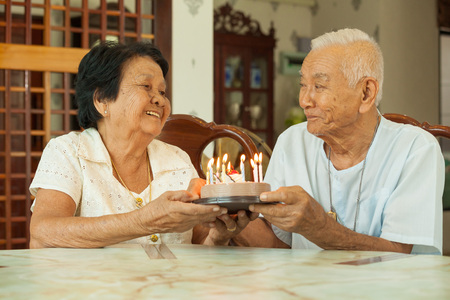 old asian: Asian senior couple holding a cake and smiling in living room