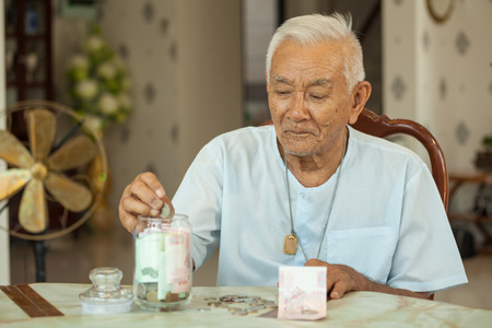 counting money: senior man counting money with glass bank