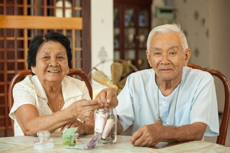 counting money: senior couple counting money with glass bank