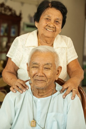 old asian: Senior woman giving a massage to her husband at home Stock Photo