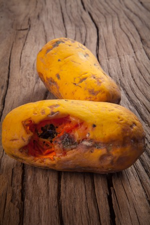 Closeup of moldy papaya fruit on wood background Stock Photo