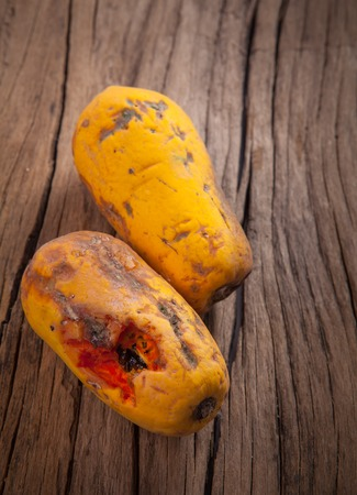 uneatable: Closeup of moldy papaya fruit on wood background Stock Photo