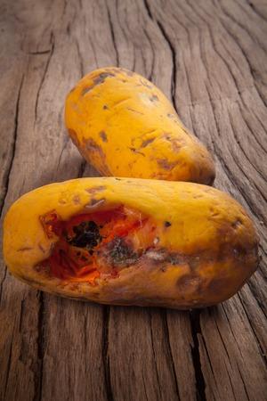 Closeup of moldy papaya fruit on wood background Stock Photo