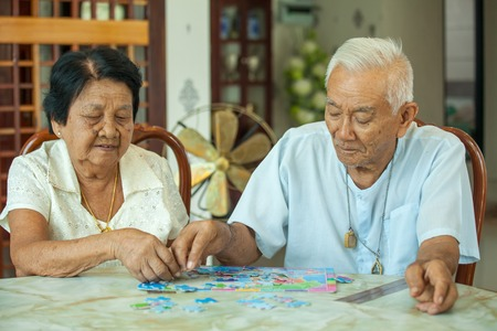 old man happy: Asian couple senior playing with a jigsaw puzzle at home