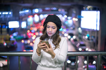 millennial: Outdoor portrait of beautiful young asian woman using her mobile phone at night. Stock Photo