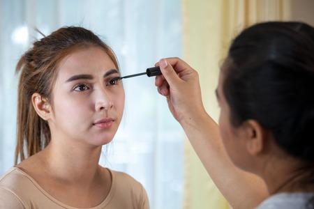 Young asian woman applying mascara on her long eyelashes photo
