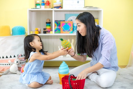 Asian mother and daughter playing toy in house Foto de archivo