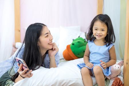 Filha e mãe Ásia gostam de jogar smartphone Foto de archivo