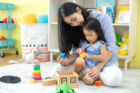 Asian mother and daughter playing toy in house Stockfoto