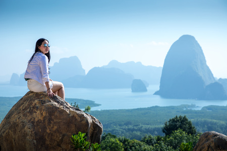 Young woman sitting on a mountain top at Phang Nga Bay from Samed Nang Chee, Thailand
