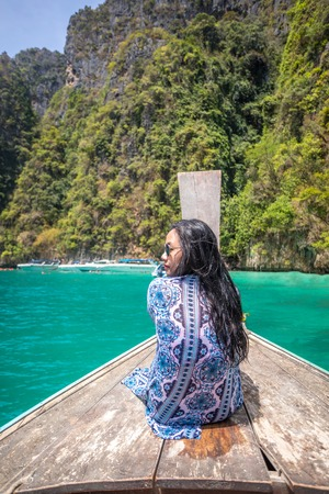 Young asian woman relax on long tail boat at Maya bay, Phi Phi island , Phuket in Thailand