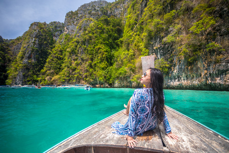 Young asian woman relax on long tail boat at Maya bay, Phi Phi island , Phuket in Thailand Stock Photo
