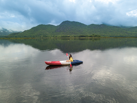 Woman kayaking on lake and mountain in Thailand 스톡 콘텐츠