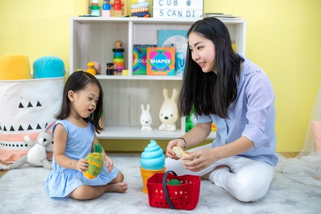 Asian mother and daughter playing toy in house 版權商用圖片