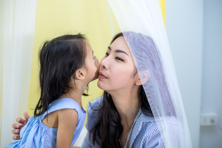Happy little asian girl kissing her mother in house