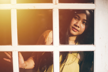 Asian woman standing at the window watching