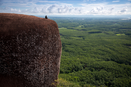 Young woman sitting on a mountain top at Phu Sing, Hin Sam Wan, Buengkan, Thailand